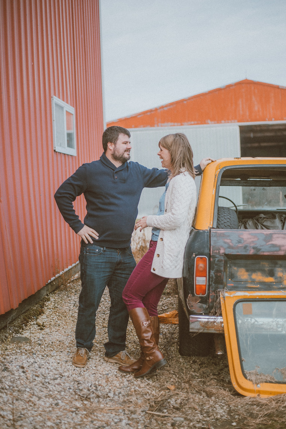 Husband and wife flirting against a car. Lifestyle couples photography by Anna Gutermuth.