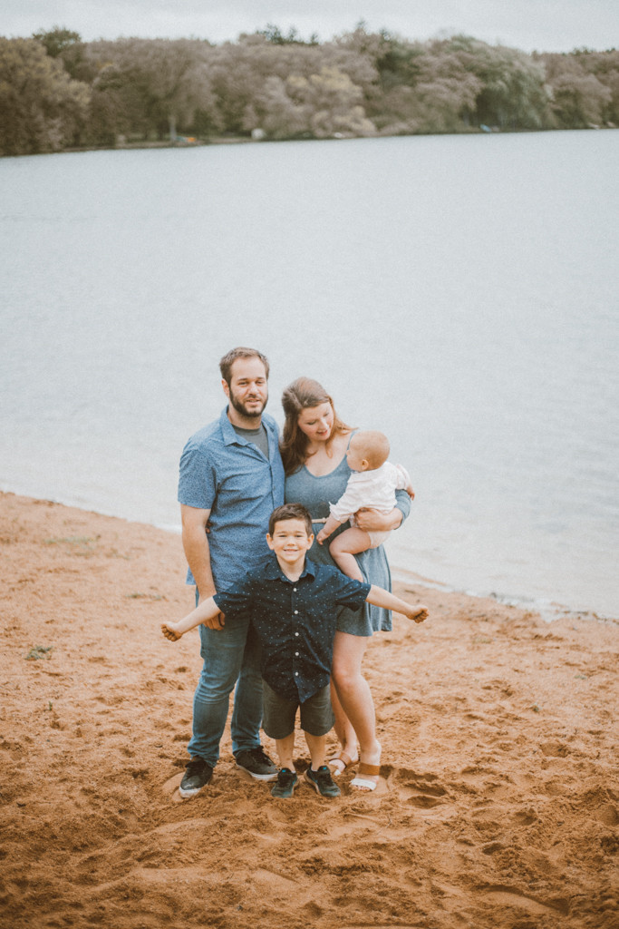 Family poses in front of Rock Lake. Lifestyle family photography in Trevor, WI.