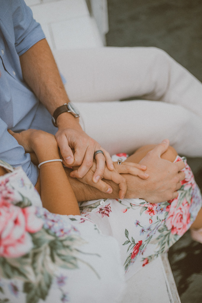 Couple holds hands while sitting on the dock at the Geneva Inn in Lake Geneva, WI. Couples photography by Anna Gutermuth.