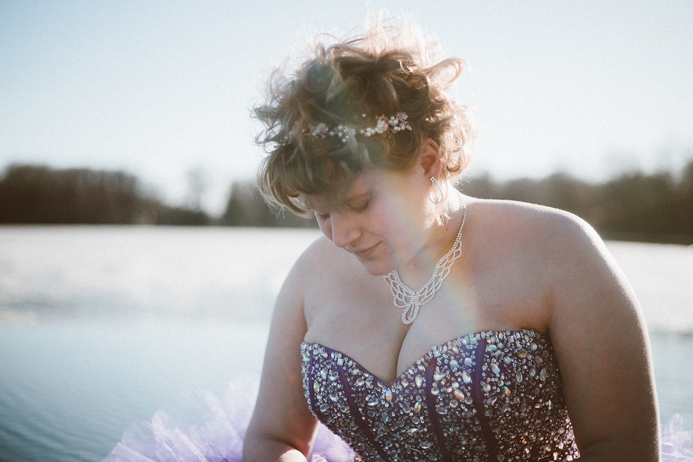 Girl in purple prom dress standing on a dock during her prom lifestyle photography session.