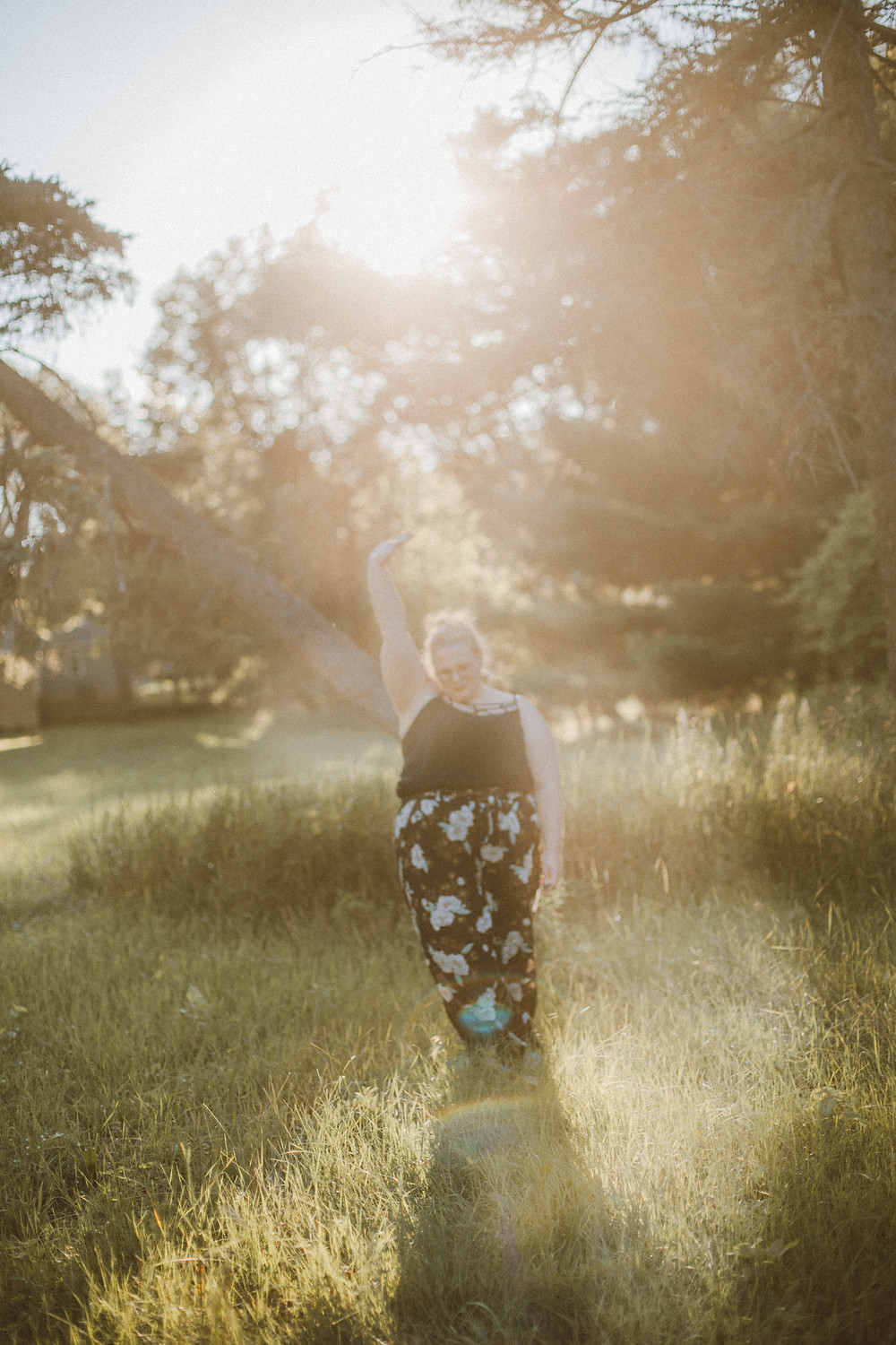 Girl in floral pants and strappy caged tank top stands in a field during golden hour.