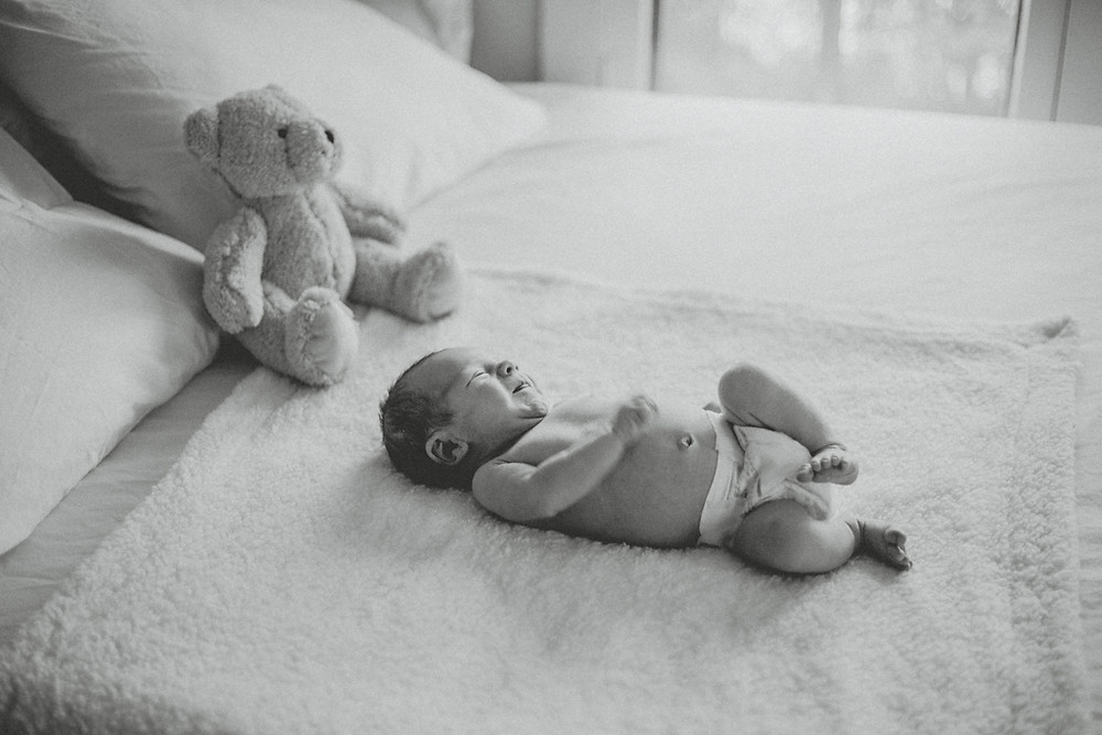 Newborn baby lays on bed. Lifestyle newborn photography by Anna Gutermuth.