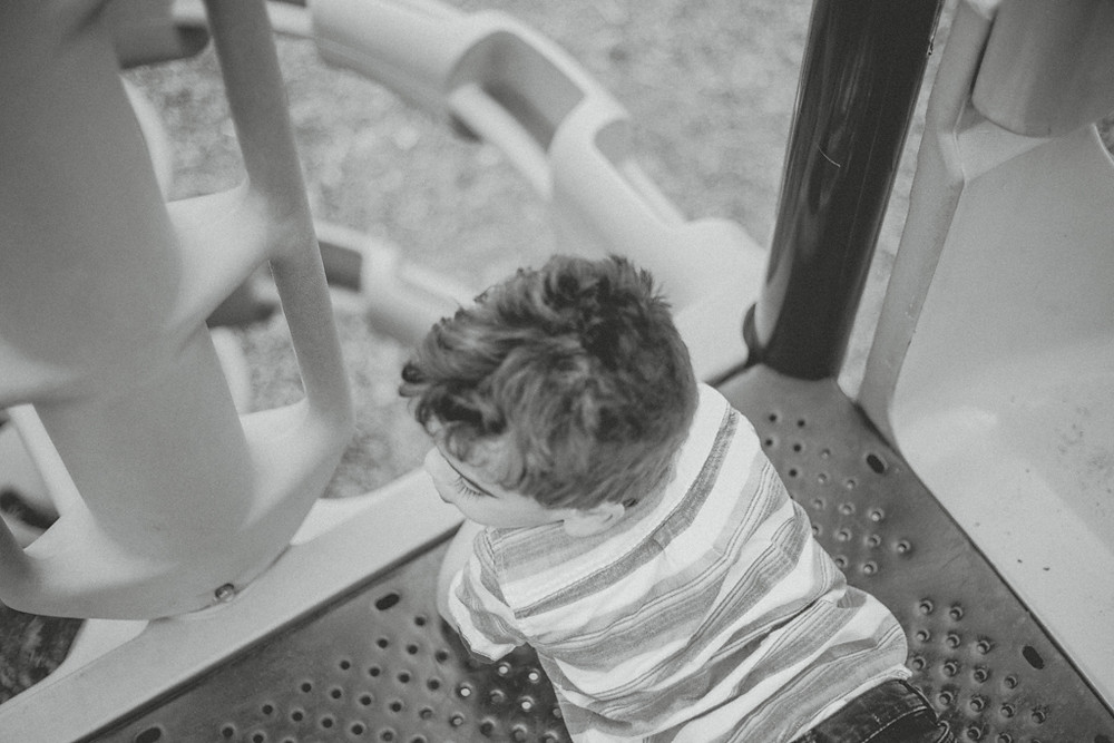 Little boy plays on the playground during a park date with mom. Family photography by Anna Gutermuth.