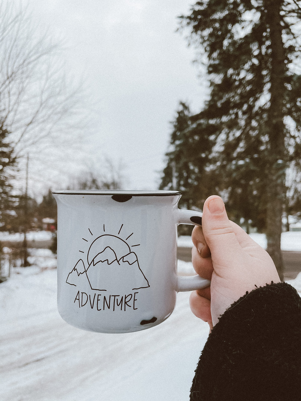 Coffee cup that says adventure looking out over a winter landscape.  Behind the scenes of Wisconsin wedding photographer Anna Gutermuth.