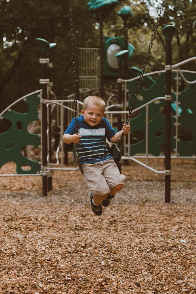 Big brother on swings. Lifestyle family photography by Anna Gutermuth.