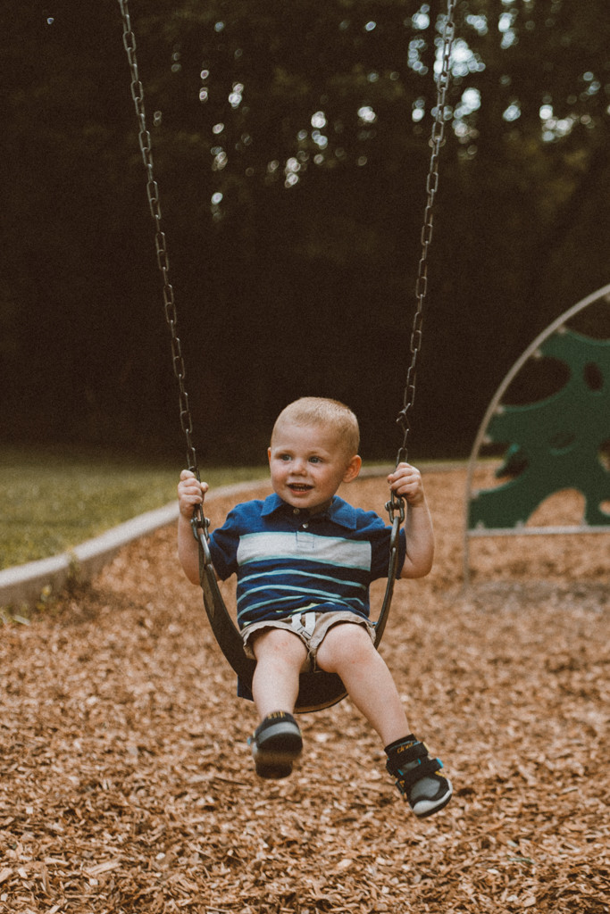 Little brother on swings. Lifestyle family photography by Anna Gutermuth.