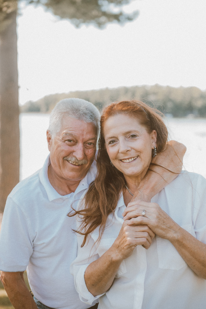 Couple smiling with their arms around each other. Lifestyle Photography by Anna Gutermuth.