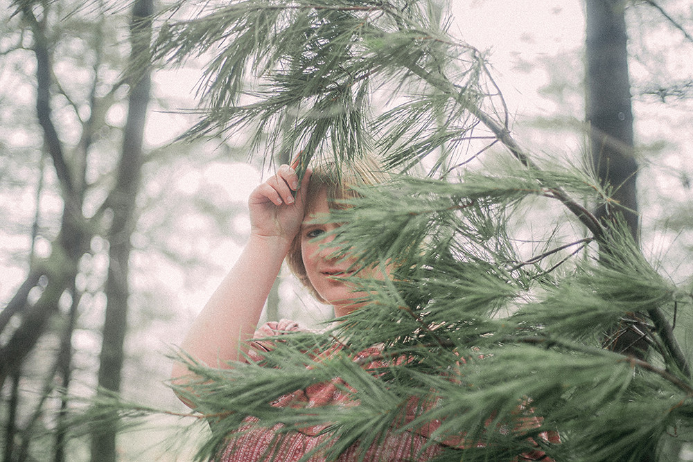 Woman holding tree branch in front of her face Wisconsin Lifestyle Photography.