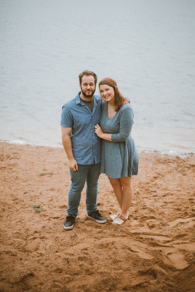 Couple poses in front of Rock Lake. Lifestyle family photography in Trevor, WI.