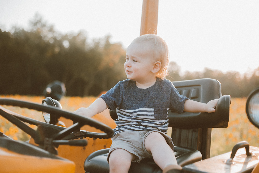 Little boy smiles on a tractor. Lifestyle Photography by Anna Gutermuth.