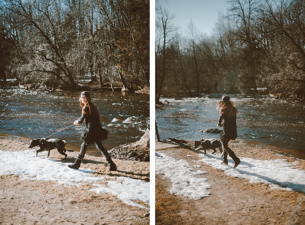 Black pitbull dog runs with red haired girl through park during their lifestyle photography session.