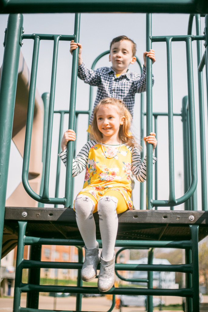 Twin siblings playing on the playground at the park during a family lifestyle photography session.