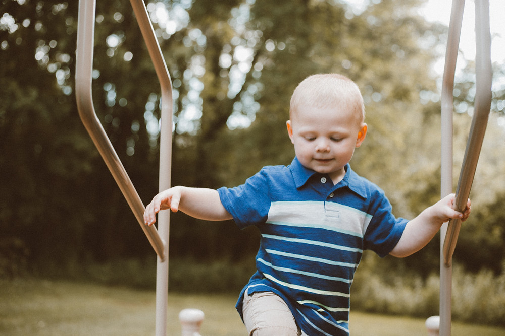 Little boy climbing playground equipment. Lifestyle family photography by Anna Gutermuth.