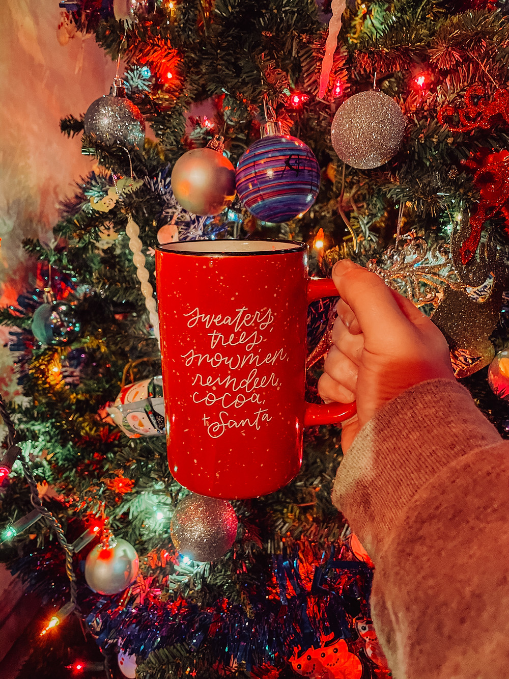 """""""Christmas things"""" mug reading sweaters, trees, snowmen, reindeer, cocoa + Santa in front of a lit and decorated Christmas tree."""