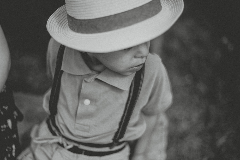 Little boy wearing a hat looking away. Lifestyle family photography by Anna Gutermuth.