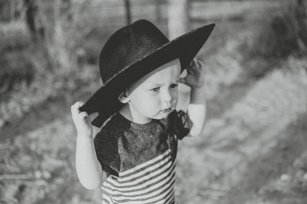 Little boy wearing a cowboy hat that's too big for him. Lifestyle Photography by Anna Gutermuth.
