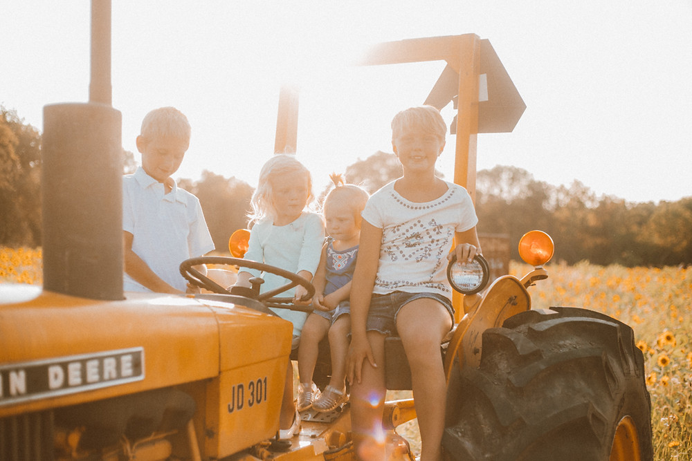 Kiddos playing on a tractor. Lifestyle Photography by Anna Gutermuth.