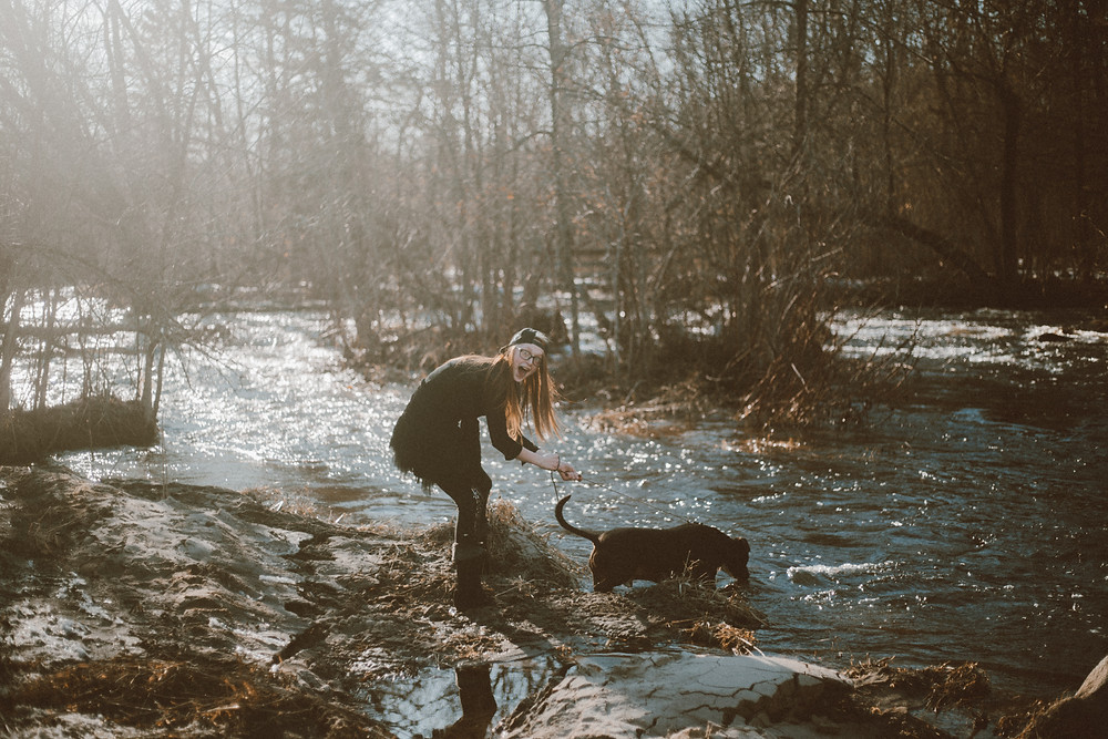 Red haired woman wades into river with black pitbull dog on leash during their lifestyle photography session.