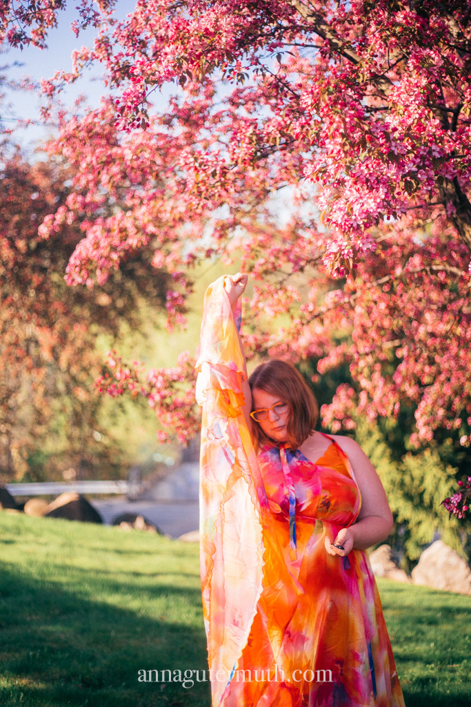 Woman in cherry blossom field shows off flowy maxi dress.