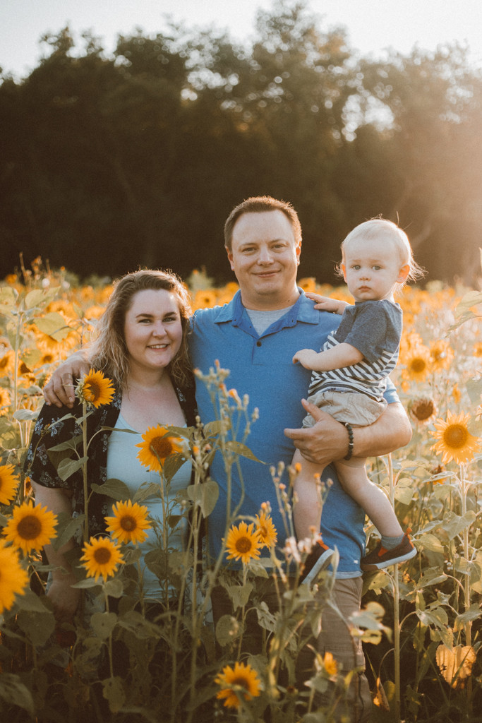 Family standing in the sunflower field. Lifestyle Photography by Anna Gutermuth.