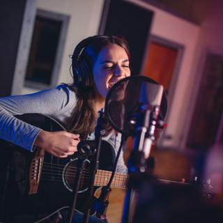Female vocal artist singing in a recordi
