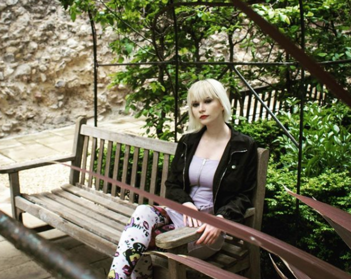 Lady with blonde hair sat on bench.PNG