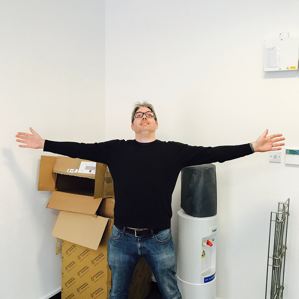 This image shows me with my arms outstretched in our new office space