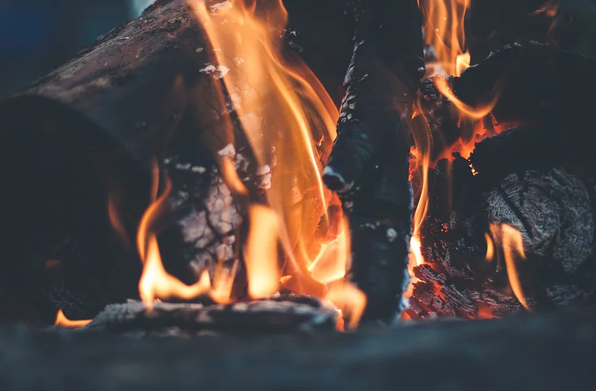 This image is a photograph of wood burning and flames on the wood pieces