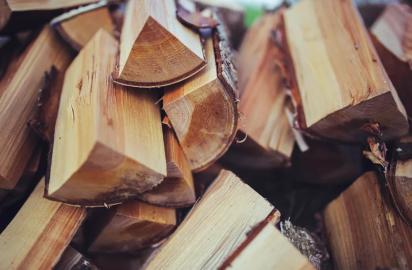 This image is a photograph of cut wood and split logs stacked in a pile