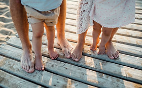 legs-and-feet-of-family-standing-on-beac
