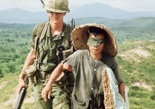 Color photo of a U.S. soldier escorting a blindfolded Vietcong prisoner during the Vietnam War in 1966