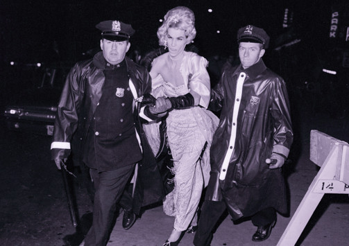 "A man dressed in an evening gown is arrested and handcuffed by police in New York City in 1962 for ""indecent exposure""."