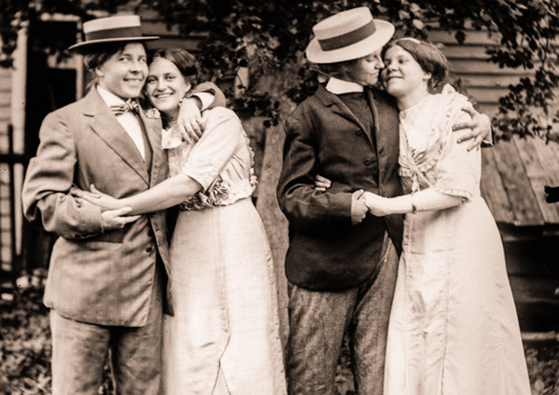 Sepia tones photo from 1920's America of two lesbian couples, two of the people dressed masculine.
