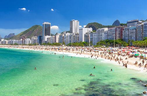 Praia de Ipanema águs cristalinas e cariocas na areia tomando banho de mar. Ao fundo prédios, Pedra da Gávea e Pão de Açúcar