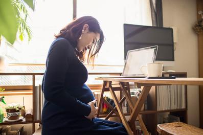 zwangere vrouw zittend achter laptop