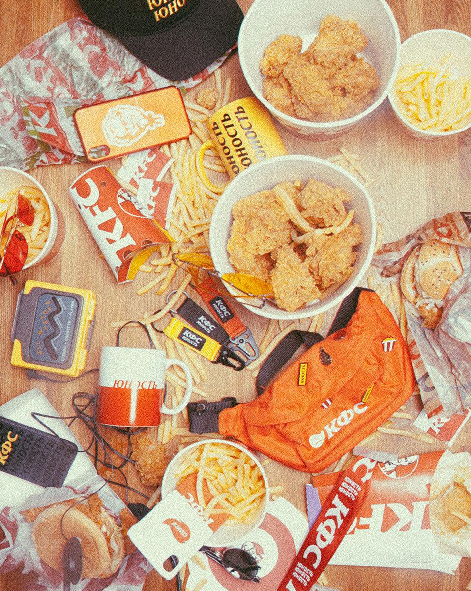 Российский бренд уличной одежды Юность и сеть ресторанов KFC выпустили совместную коллекцию одежды.   Центральной темой коллаборации стало переосмысление визуальных архивов KFC: полковника Сандерса и фирменной цветовой палитры. В коллекцию вошли куртки, футболки, худи, свитшоты, сумки и конечно же носки с кириллической надписью «КФС».  По словам представителей бренда, при создании коллекции за основу были взяты классические силуэты спортивной одежды конца 80-х - начала 90-х годов и минималистичный дизайн, исполненный в цветовой гамме, дополненной айдентикой бренда KFC.   В коллекции использовано первое винтажное изображение полковника Сандерса как отсылка к началу, истории, юности бренда KFC. Цвета коллекции, лаконичный дизайн, коллаборация марок из совершенно разных отраслей, мировых брендов с локальными, эксперимент с андеграундом и стилем 80–90-х годов.