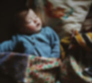 Dark haired baby sleeping with a Kantha Bae pareo blanket, blue cardigan and chicken cushion