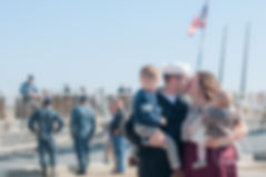 navy famil kissing in front of ship after deployment