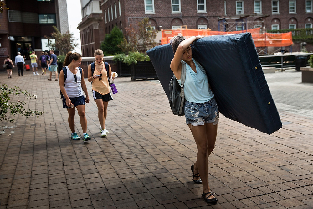 Emma Sulkowicz carries a mattress in protest of the university's lack of action after she reported being raped during her sophomore year. (Photo by Andrew Burton/Getty Images)