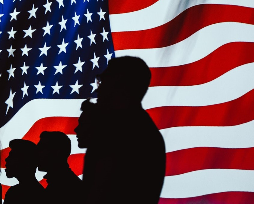 People silhouetted against American Flag Photo by Brett Sayles from Pexels