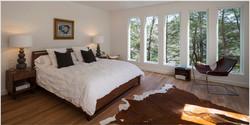 New-york-area-rug-chair-cowhide-rug-cushions-desk-lamp-framed-art-hardwood-floor