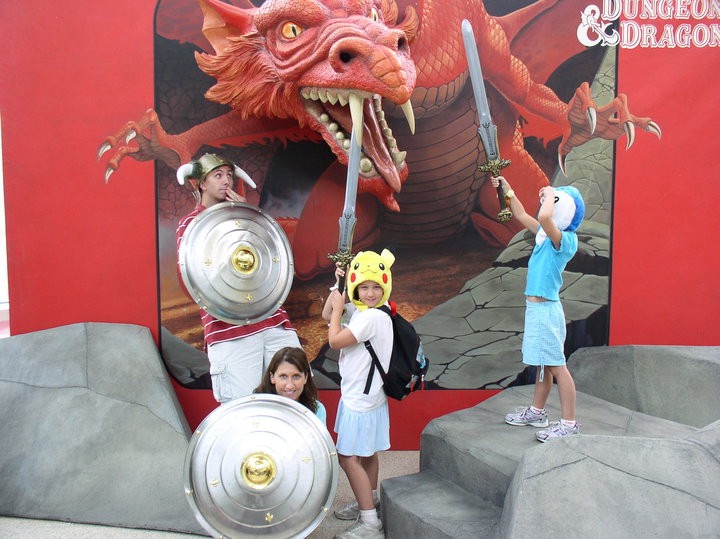 Family posing with swords in front of a 3D dragon background.