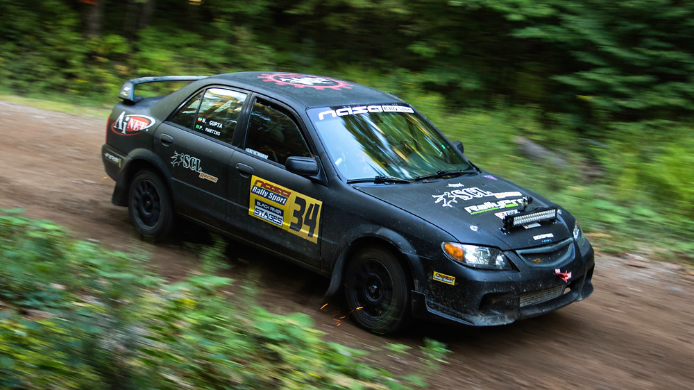 SCL Racing Rally Mazda Protege driving in the forest at Black River Stages