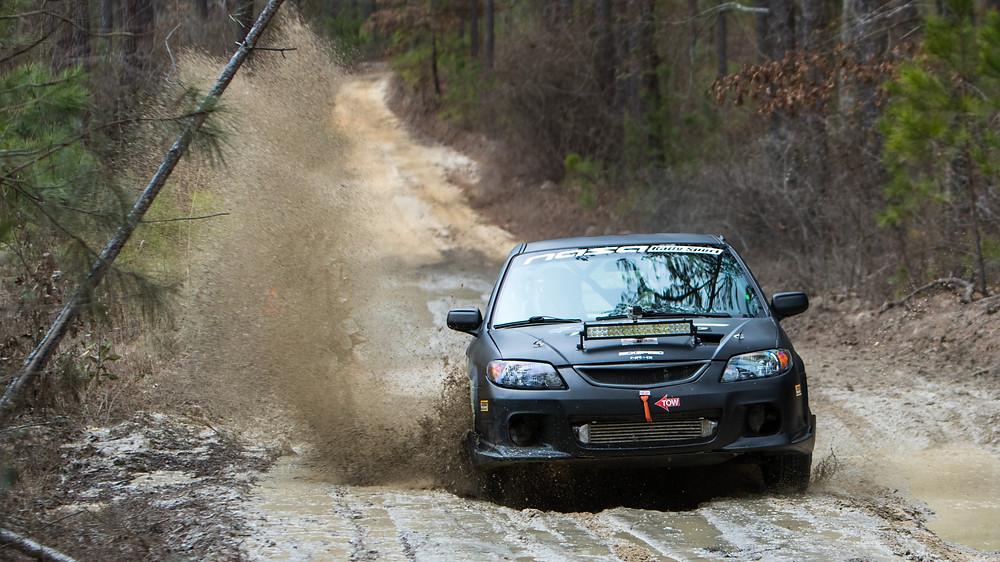 SCL Racing Rally Mazda Protege splashing water and mud at the Sandblast rally