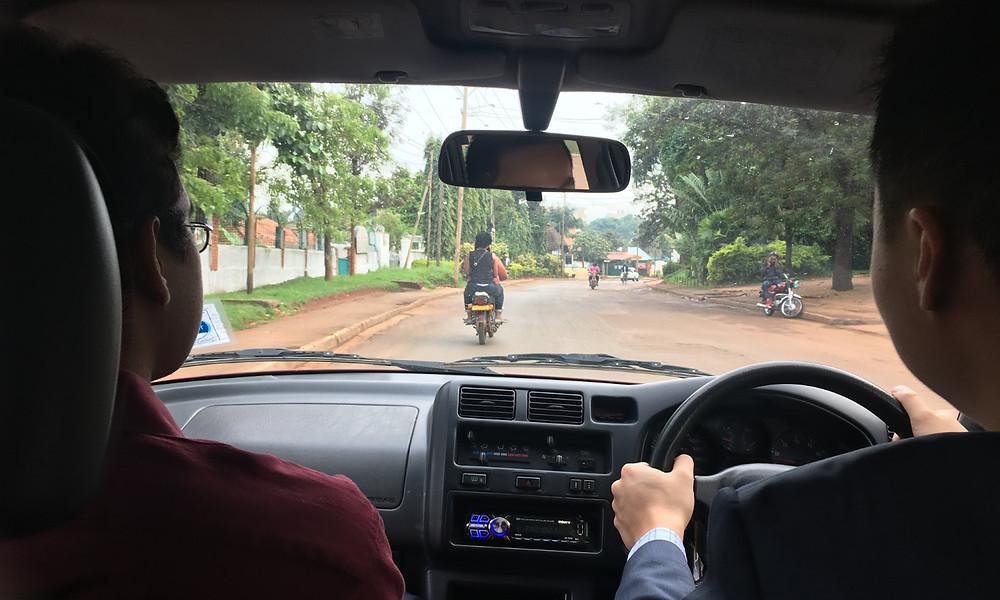 Jae and Gautam driving in Uganda