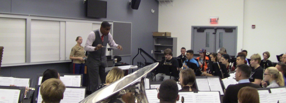 Gunnery Sergeant Justin Hauser of the Marines directs a group of ARCC students with Marine Band players.