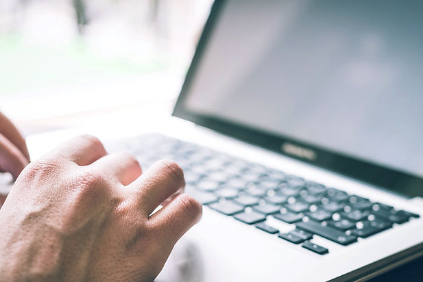 A silver laptop keyboard in the background with its screen just visible to the right. Someone is typing on the keyboard- we can see their fingers.