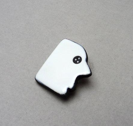 petite broche en forme de tête ou visage blanc et noir