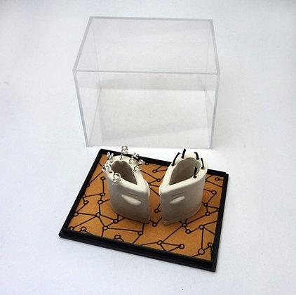petits personnages en céramique blanche dans une boîte vitrine fond ocre