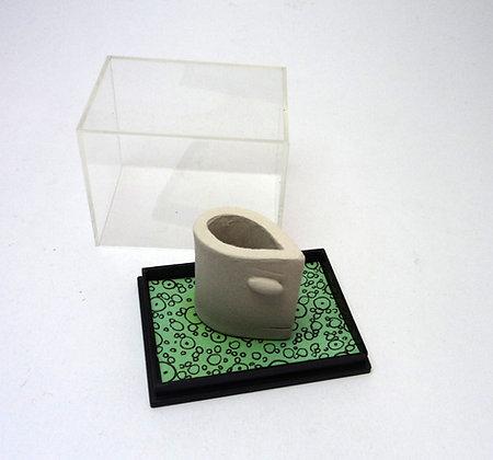 sculpture personnage blanc en céramique sur sol vert graphique à pois